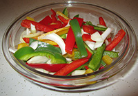 Bowl of sliced peppers and onions