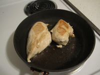 Pan with chicken breast frying